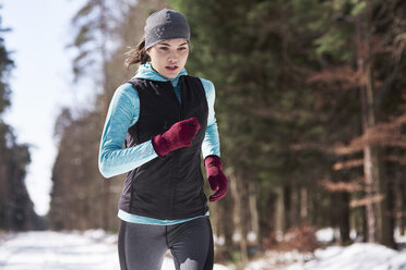 Young woman jogging in winter forest - ABIF00291