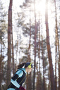 Young woman with headphones jogging in winter forest - ABIF00294