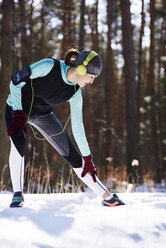 Young woman with headphones doing tretching exercise in winter forest - ABIF00297