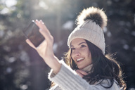 Portrait of smiling young woman taking selfie with smartphone in winter forest - ABIF00300