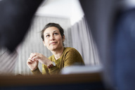 Confident businesswoman looking at female colleague while sitting in board room - MASF01855