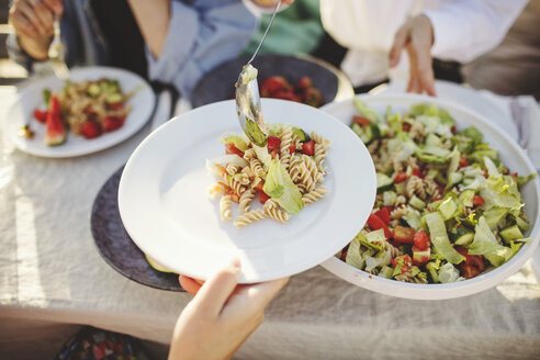 Close-up of woman serving pasta to friend at picnic table - MASF01864