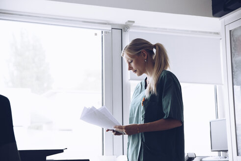 Female nurse reading documents while standing against window at doctor's office - MASF01903