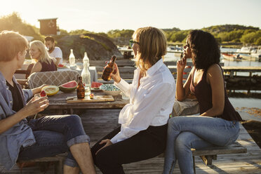 Friends enjoying lunch at picnic table on jetty during summer - MASF01906