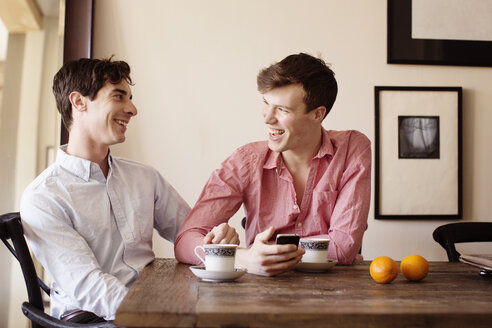 Happy gay couple sitting by table at home - CAVF35462