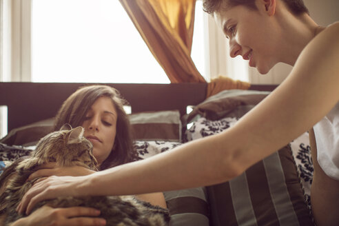 Women looking at cat while relaxing on bed at home - CAVF35492