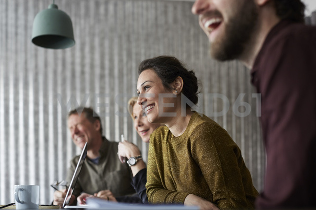 Cheerful creative business colleagues sitting at conference table while looking away in board room - MASF01931