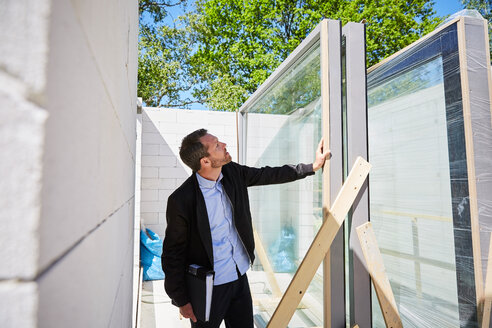 Architect with file analyzing at construction site on sunny day - MASF01934