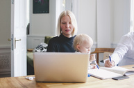 Businesswoman with baby girl using laptop at table in creative office - MASF01943