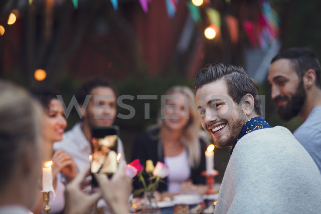 Woman photographing man while sitting with friends at garden party - MASF01955 - Maskot ./Westend61