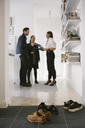 Various shoes on floor with female realtor discussing with young couple by shelves in background - MASF01985