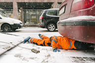 Tow truck driver lying on road by car in city during winter - MASF01991