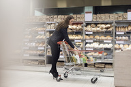 Woman keeping paper bag in shopping cart while standing by bread rack at supermarket - MASF02000