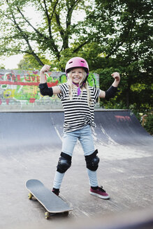 Smiling girl flexing muscles while standing on skateboard ramp - MASF02006