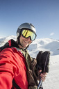 Smiling man in ski-wear standing on snow covered field against clear sky - MASF02009