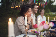 Smiling friends sitting at decorated table in garden party - MASF02012