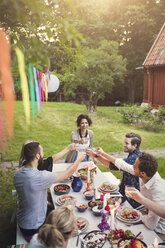 Smiling woman toasting drink with friends at table in garden party - MASF02015