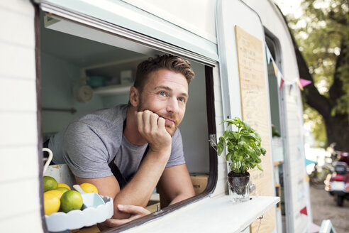 Thoughtful male owner looking out through food truck window - MASF02021