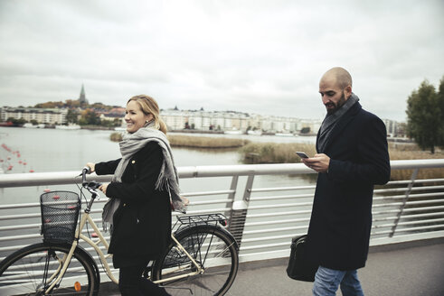 Smiling businesswoman with bicycle walking by businessman on bridge - MASF02027