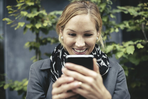 Smiling mid adult businesswoman using smart phone outdoors - MASF02030