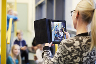 Teacher photographing students through digital tablet in school - MASF02036