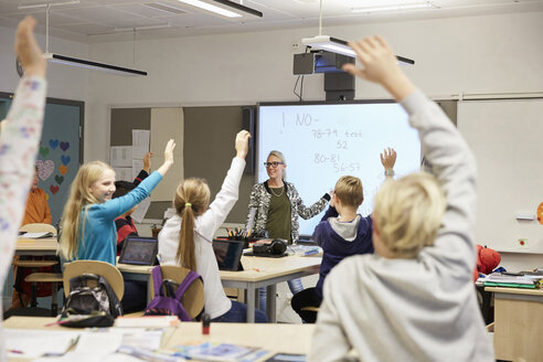 Teacher looking at students with hands raised in classroom - MASF02039