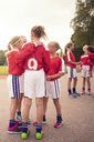 Soccer girls talking while standing on footpath against sky - MASF02048