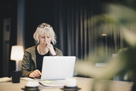 Thoughtful businesswoman using laptop at desk in office - MASF02054