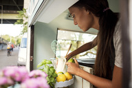 Side view of female owner holding lemon while working in food truck - MASF02066