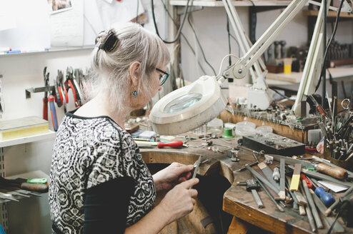 Side view of senior woman making jewelry at workbench in workshop - MASF02078