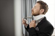 Side view of businessman fastening necktie against window in hotel room - MASF02081