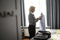 Side view of businesswoman holding shirt against window at hotel room - MASF02087
