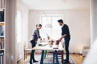 Side view of couple arranging objects on dining table at home - MASF02090