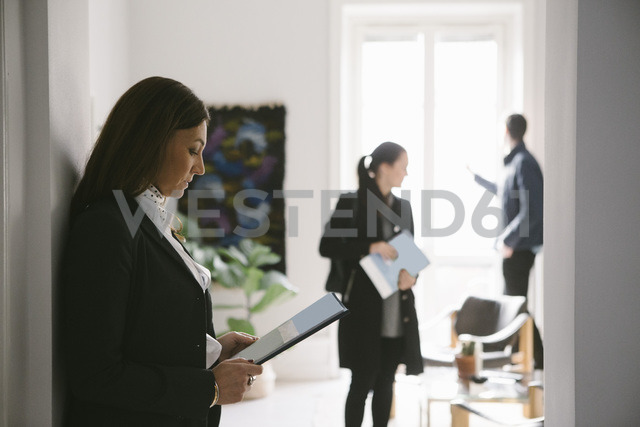 Side view of female realtor reading brochure with couple in background - MASF02093