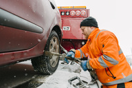 Side view of driver attaching car tire with equipment on tow truck - MASF02096