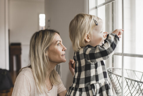 Side view of mother and daughter looking through window at home - MASF02102