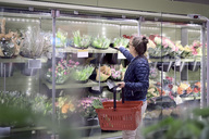 Side view of woman buying flowers from glass cabinet at supermarket - MASF02105