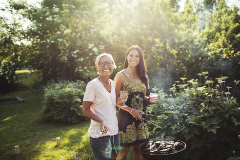 Portrait of happy women standing by barbecue grill at back yard on sunny day - MASF02115
