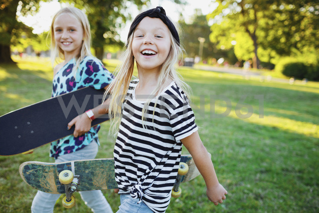 Portrait of happy friends carrying skateboards while walking on grassy field - MASF02121