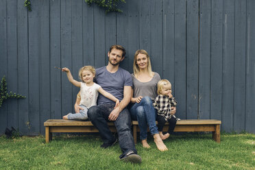 Portrait of happy parents and children sitting on seats against fence at yard - MASF02154