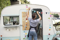 Rear view of male owner hanging bunting on food truck - MASF02166