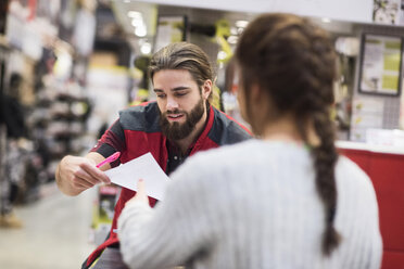 Salesman giving document to female customer in hardware store - MASF02169