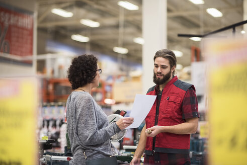 Salesman discussing with female customer holding document in hardware store - MASF02172