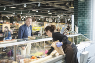 Saleswoman selling food to mature man in organic supermarket - MASF02175