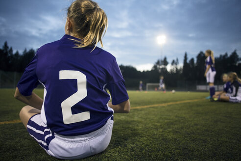 Rear view of girl sitting on field against sky - MASF02181