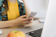 Close-up of woman sitting at table at home using cell phone and laptop - KKAF00915