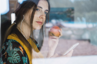 Young woman with earphones, cell phone and apple looking out of window - KKAF00924