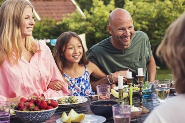 Playful man sitting with girls at dining table in back yard - MASF02198