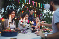 Multi-ethnic friends enjoying meal in back yard at garden party - MASF02210