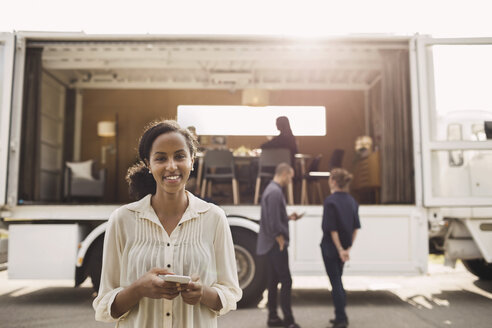 Portrait of confident businesswoman holding smart phone with colleagues and portable office truck on road in background - MASF02222